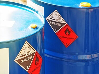 two large blue containers of corrosive flammable liquid chemicals
